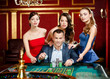 Man surrounded by girls plays roulette at the casino