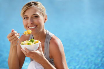 Woman eating fruit cocktail by swimming pool