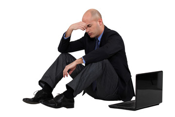 Stressed out businessman with his laptop