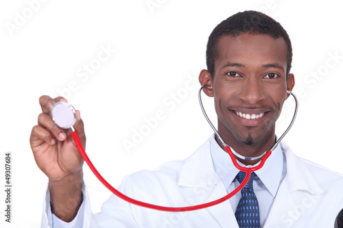 Smiling doctor holding aloft his stethoscope