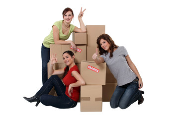 Three women gathered by cardboard boxes
