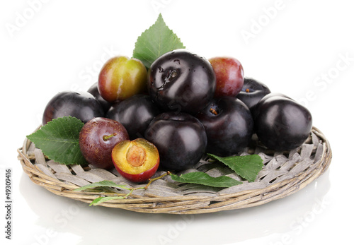 Rip plums on the wicker cradle isolated on white