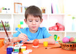 Cute little boy painting easter eggs