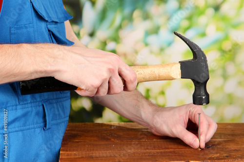 Builder hammering nails into board on natural background