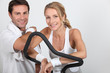 Couple wearing sportswear stood by exercise bike