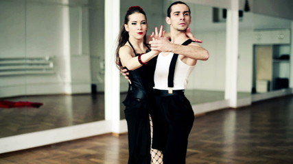 Montage of professional dancers dancing tango in ballroom