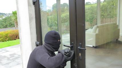 Burglar opening lock on door