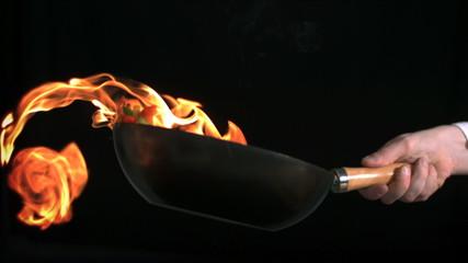 Man flambeing vegetables in pan