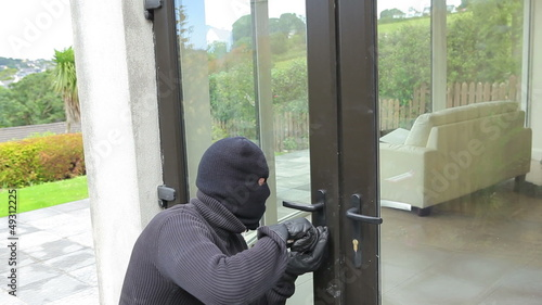 Burglar opening lock on door