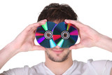 Young man holding compact discs to his face