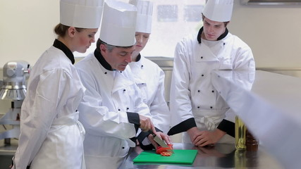 Chefs at the counter learning how to slice vegetables