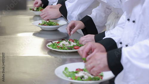 Four cooks at the counter preparing salad