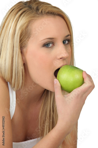 Young woman biting into a crisp green apple