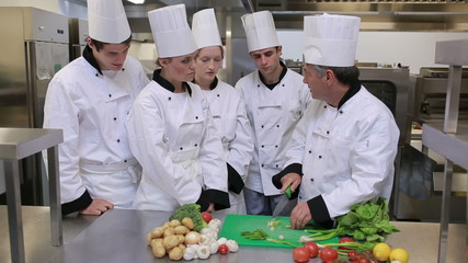 Cooks standing in a kitchen and learning to slice vegetables