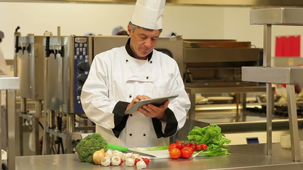 Chef using a tablet computer for taking notes