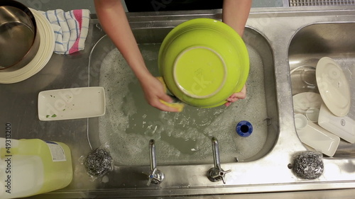 Cleaner washing the dishes at a sink