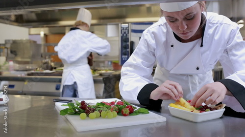 Cook at a counter making a fruit salad