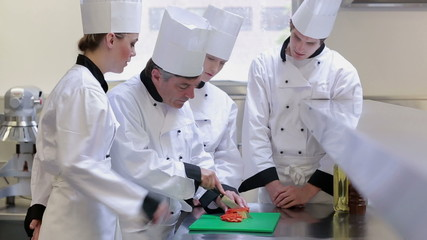 Trainee chefs learning how to slice vegetables