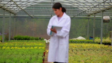 Woman standing at the greenhouse holding a clipboard