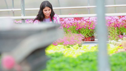 Woman working at the greenhouse smiling