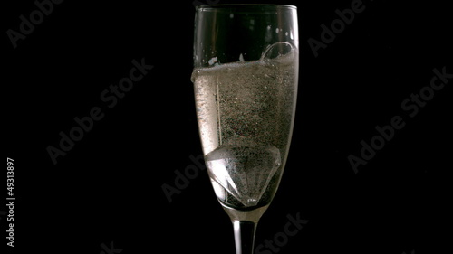 Ice cube dropping into champagne flute