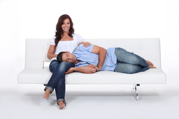 Sleeping man with his head on his girlfriend's lap