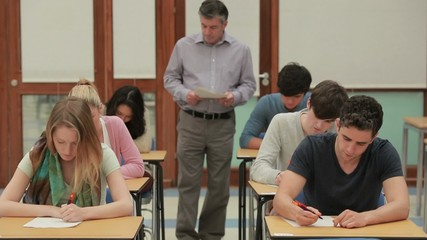 Students doing a test while teacher walk arround