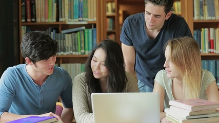 Four students with a laptop in a library