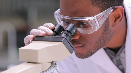 Student looking through microscope while one is watching