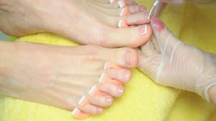Cosmetician painting toenails
