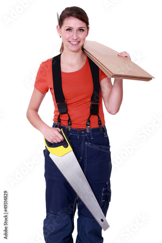 Woman carrying plywood and a saw