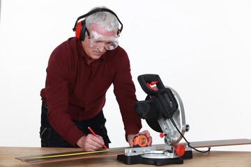 A mature carpenter taking measures.