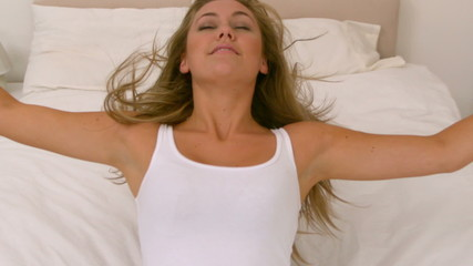 Blonde woman bouncing on her bed