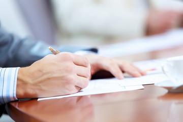 Hands of businessman writing