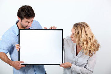 Man and woman astounded by a board left blank for your image