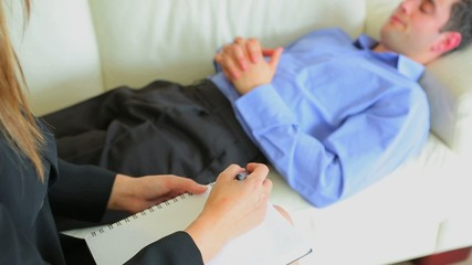 Therapist taking notes while patient lying on the sofa
