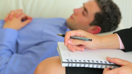 Man lying on a sofa while with therapist making notes