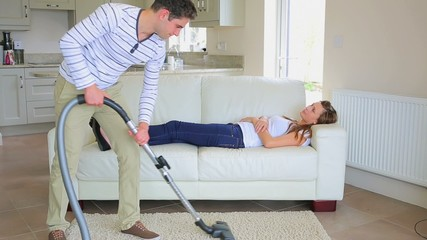 Woman sleeping on the sofa while man doing the housework