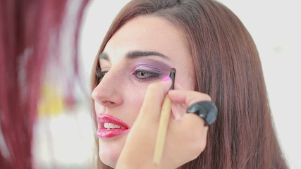Woman getting eye shadow applied