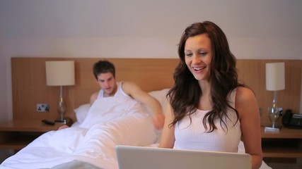 Woman on her laptop in her bed