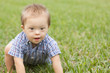 Down Syndrome child crawling in green grass - 49316878