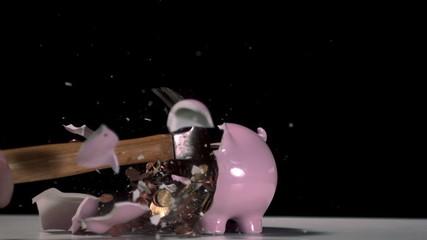 Hammer breaking a piggy bank