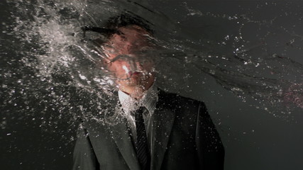 Man in suit being splashed with water