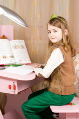 Smiling young girl working at her desk