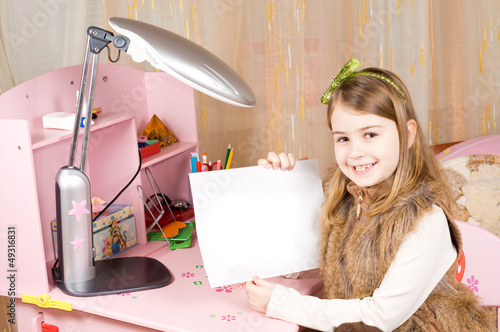 Cute little girl showing blank paper