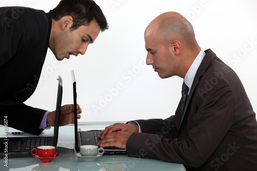 Businessman sneaking a peak at his colleague's work