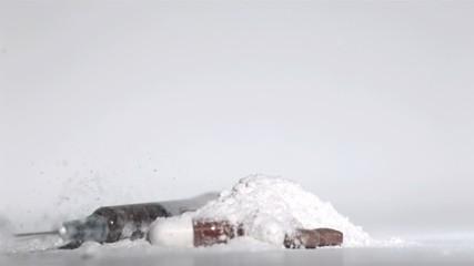 Syringe falling on white drug with pills
