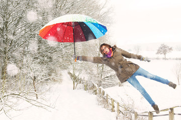 girl with colored umbrella flying of a winter landscape