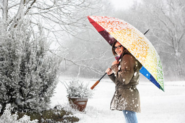 girl with colored umbrella standing in snowfall