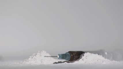Syringe falling into powdered drug